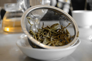 white bowl with tea leaves in a strainer