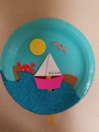 blue paper plate with foam water, boat, sun, crab, and sea gull